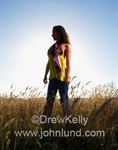 Photo of a strong hispanic woman standing in a field of grain and perhaps facing her future.